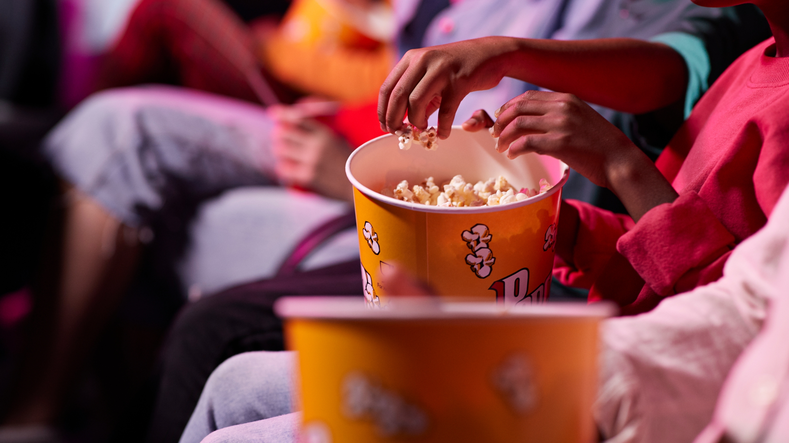 Friends share popcorn in a theater. (Getty Images)
