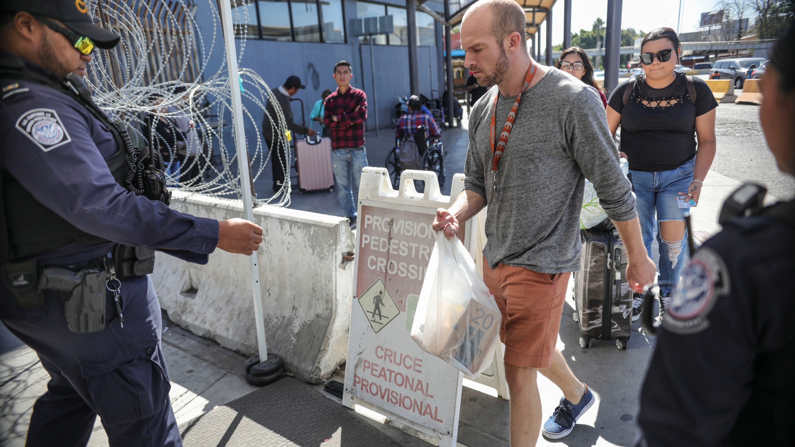 An Immigration and Customs Enforcement (ICE) agent check pedestrians' documentation at the San Ysidro Port of Entry on Oct. 2, 2019 in San Ysidro, California. (SANDY HUFFAKER/AFP via Getty Images)