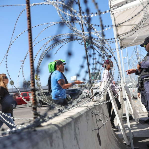 An immigration agent checks pedestrians' documentation at the San Ysidro Port of Entry on Oct. 2, 2019. (Credit: Sandy Huffaker / AFP / Getty Images)