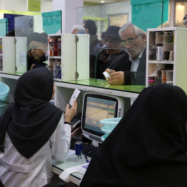 """Iranians wait to get prescription drugs at the state-run """"13 Aban"""" pharmacy in Tehran on Feb. 19, 2020. (ATTA KENARE/AFP via Getty Images)"""