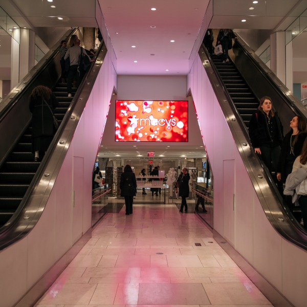 Shoppers pass by an illuminated sign inside the Macy's flagship store on 34th Street in Midtown Manhattan on Feb. 25, 2020. (Scott Heins/Getty Images)