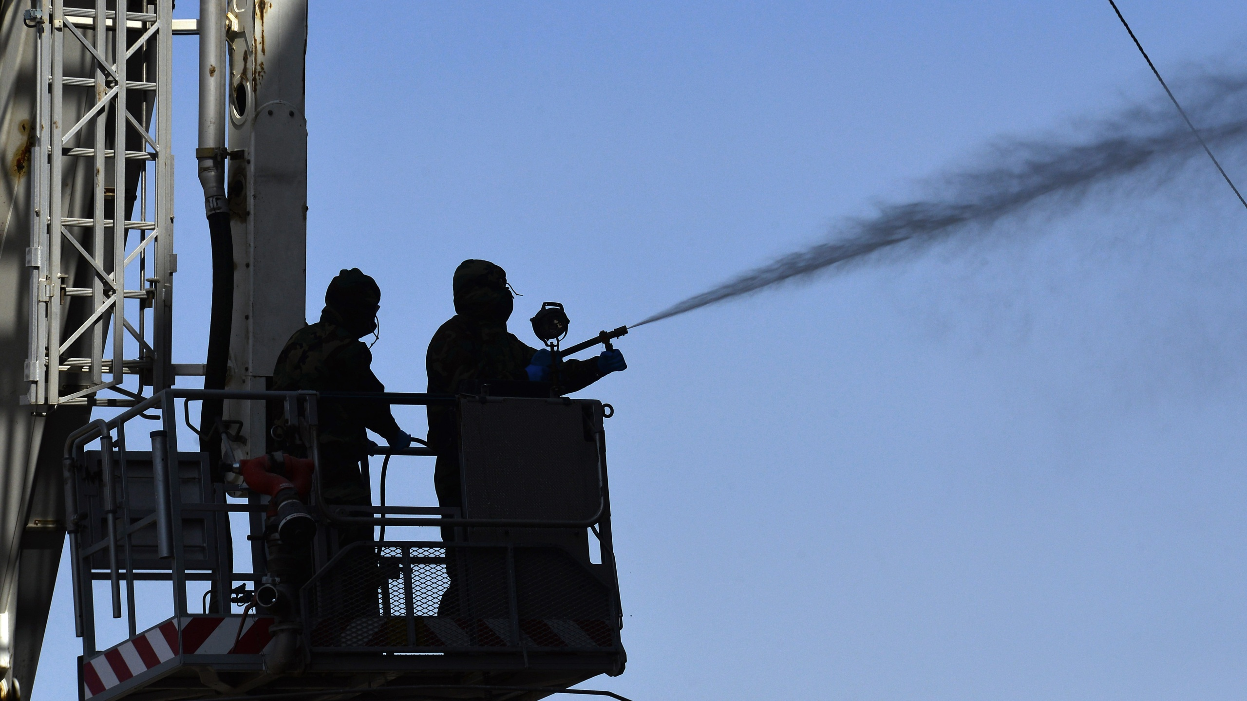 Members of the Iraqi civil defense spray disinfectant on and around a building where Islamic students are quarantined for having had contact with Iraq's first confirmed case of novel coronavirus infection, in the central holy city of Najaf, on Feb. 26, 2020. (Haidar HAMDANI / AFP) (Photo by HAIDAR HAMDANI/AFP via Getty Images)