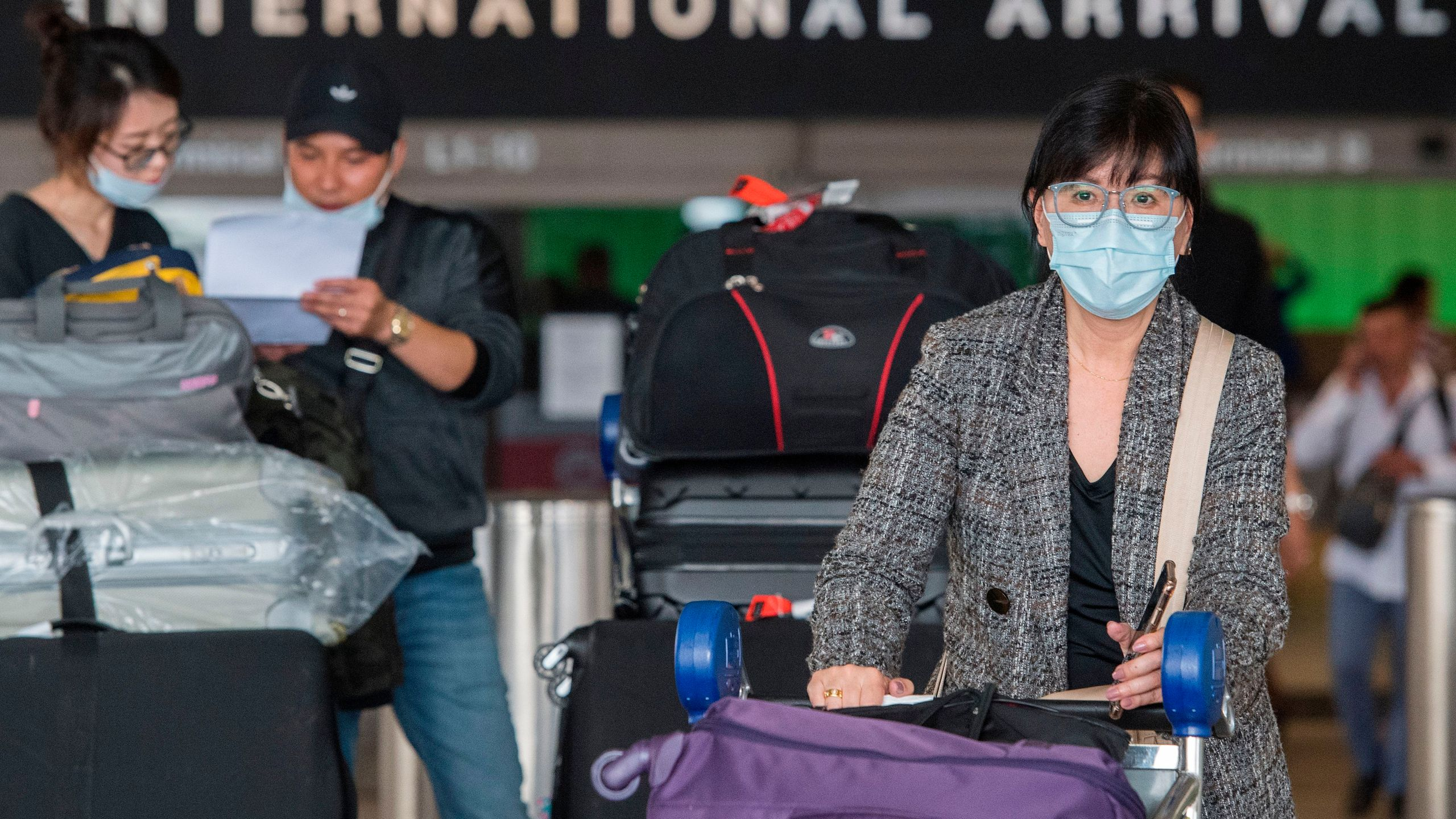 Passengers wear face masks to protect against the spread of the COVID-19, coronavirus, as they arrive at LAX on Feb. 29, 2020. (Mark Ralston/AFP via Getty Images)