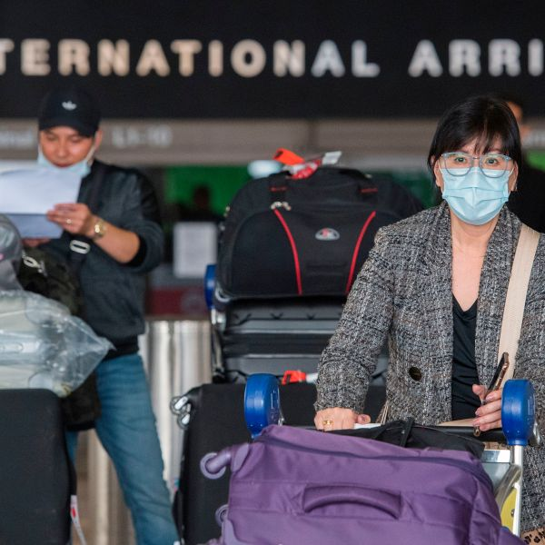 Passengers wear face masks to protect against the spread of COVID-19 as they arrive at LAX on Feb. 29, 2020. (Mark Ralston/AFP via Getty Images)