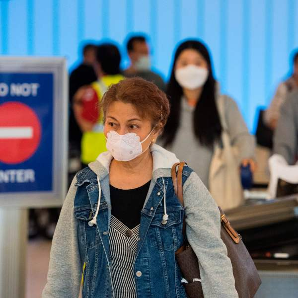 Passengers wear face masks to protect against the spread of the novel coronavirus as they arrive at Los Angeles International Airport on Feb. 29, 2020. (Credit: Mark Ralston / AFP / Getty Images)