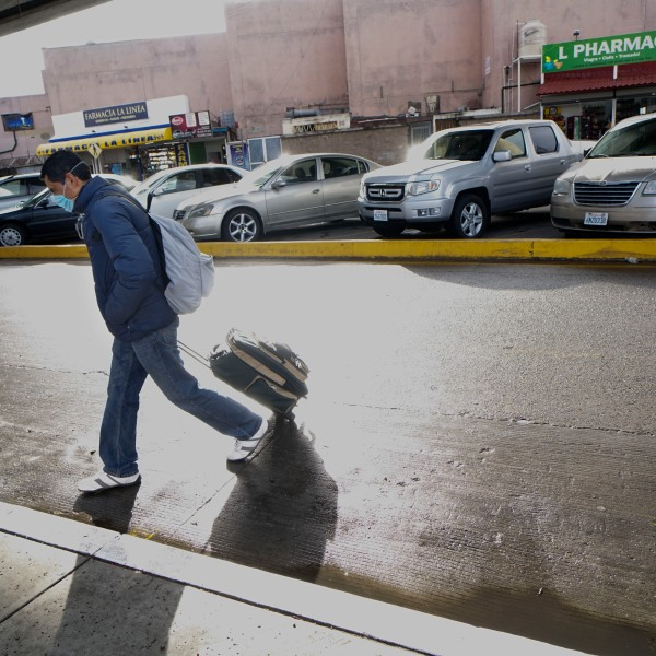A man wearing a mask walks to cross the border at the El Caparral crossing in Tijuana on March 2, 2020. (Credit: Sandy Huffaker / Getty Images)