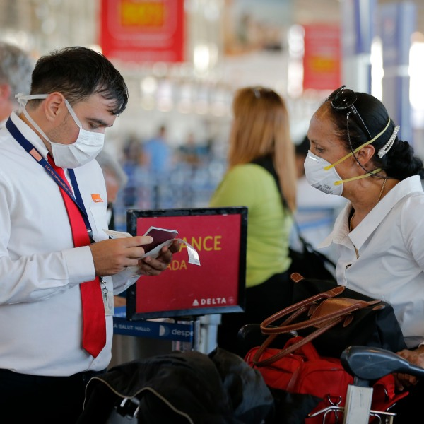 An airline staff member wears a protective mask while working at the Arturo Merino Benitez International Airport, in Santiago, on March 3, 2020.(Javier Torres/AFP via Getty Images)