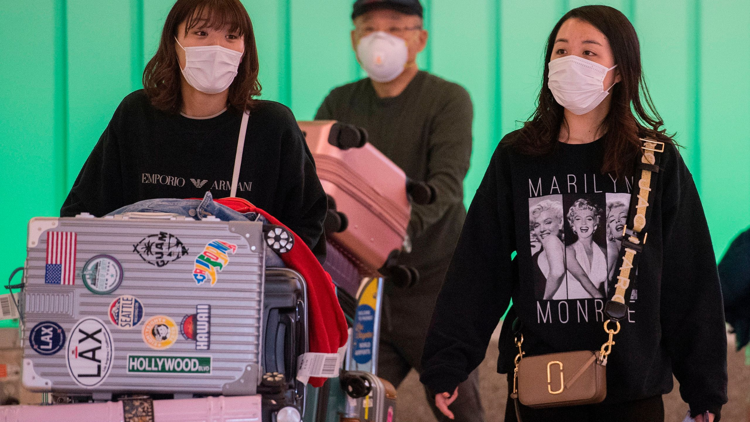 Passengers wear face masks to protect against the COVID-19 (Coronavirus) after arriving at Los Angeles International Airport in Los Angeles on March 5, 2020.(MARK RALSTON/AFP via Getty Images)