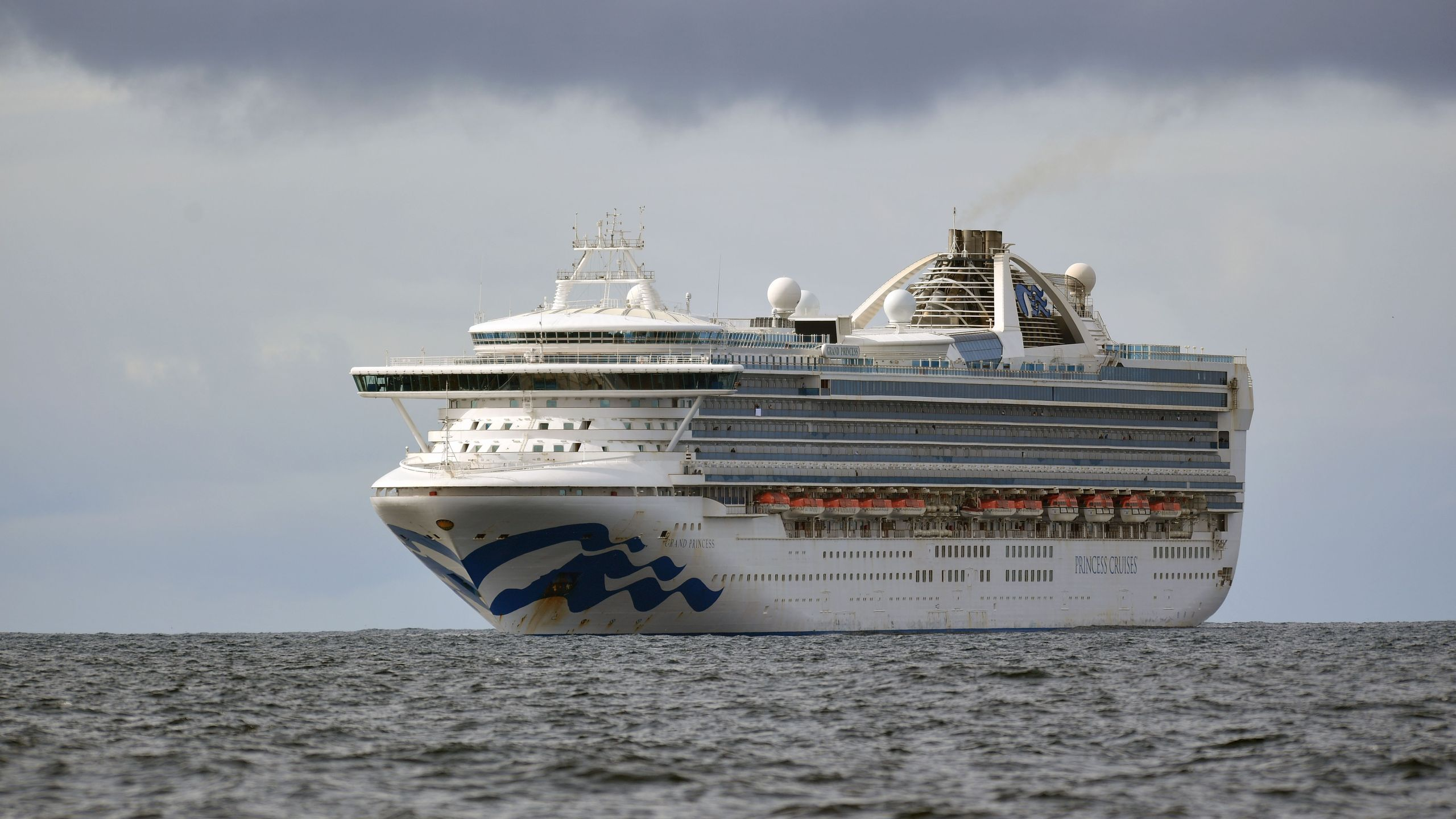 People look out from aboard the Grand Princess cruise ship, operated by Princess Cruises, as it maintains a holding pattern about 25 miles off the coast of San Francisco, California on March 8, 2020. (JOSH EDELSON/AFP via Getty Images)