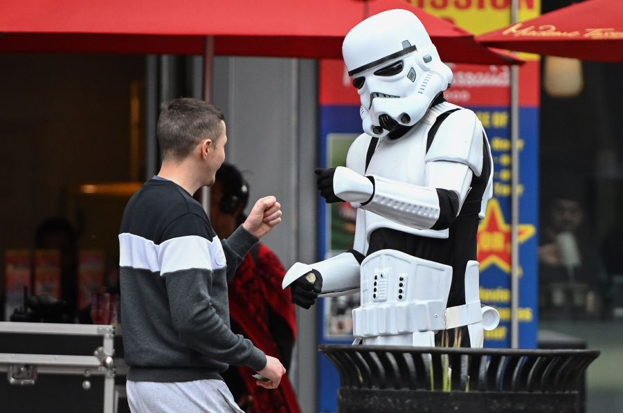 A person in a Stormtrooper costume who poses for snapshots with tourists in exchange for tips fist bumps with a passerby, on the Hollywood Boulevard on March 10, 2020. Fist bumps are being encouraged by health officials to avoid the spread of COVID-19. (ROBYN BECK/AFP via Getty Images)