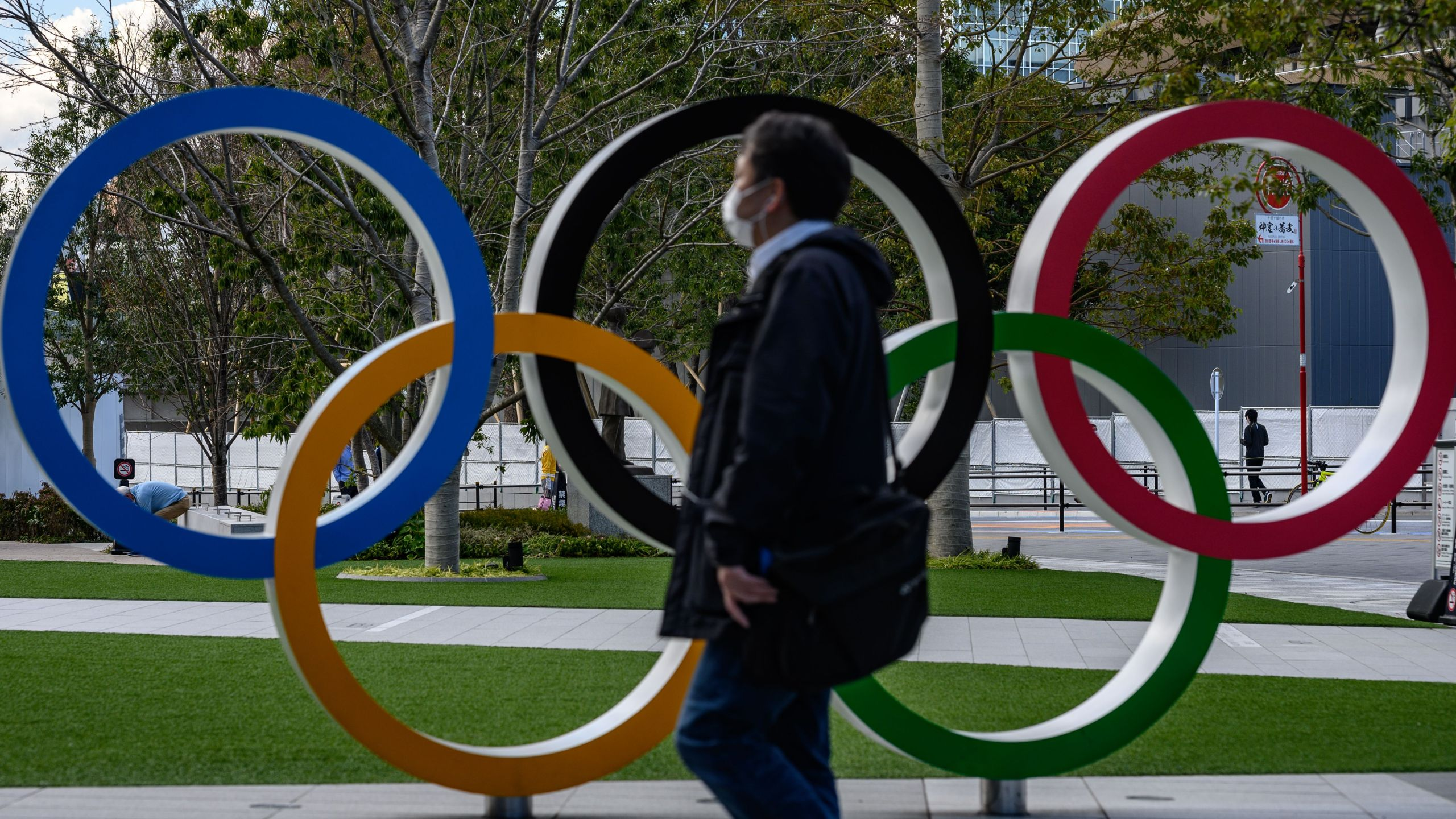 A man wearing a face mask walks in front of the Olympic Rings in Tokyo on March 11, 2020. (Philip Fong/AFP via Getty Images)
