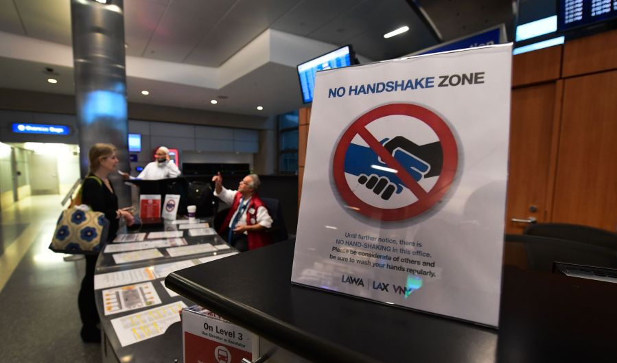 A traveler speaks to a worker at an information booth beside a reminder not to shake hands over coronavirus concerns at Los Angeles International Airport on March 12, 2020. (FREDERIC J. BROWN/AFP via Getty Images)