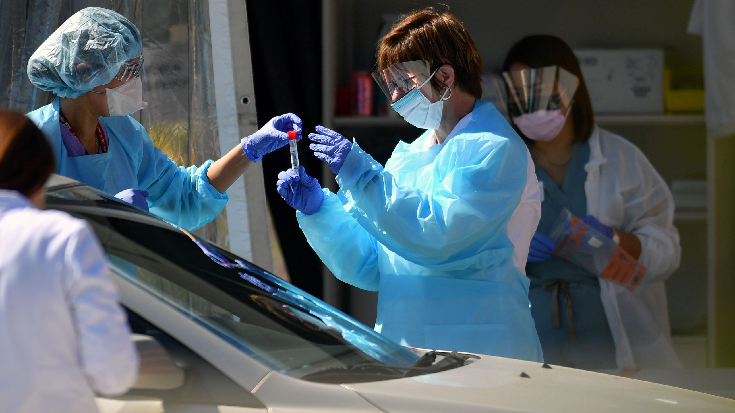 Medical workers at a Kaiser Permanente French Campus test a patient for the novel coronavirus, COVID-19, at a drive-thru testing facility in San Francisco on March 12, 2020. (JOSH EDELSON/AFP via Getty Images)