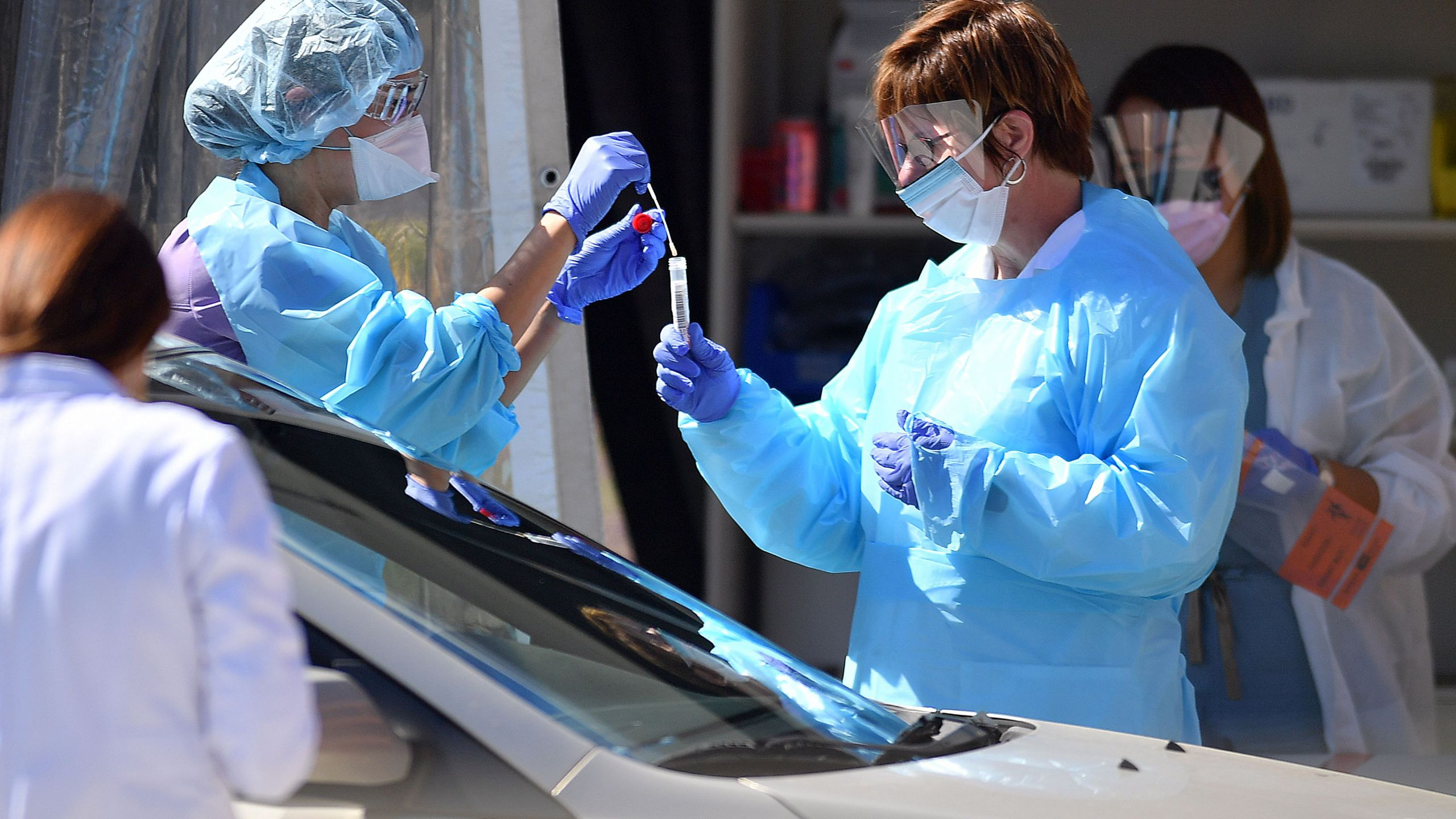 Medical workers at Kaiser Permanente French Campus test a patient for the novel coronavirus, COVID-19, at a drive-thru testing facility in San Francisco on March 12, 2020. (JOSH EDELSON/AFP via Getty Images)