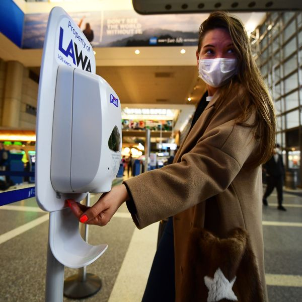 A woman wearing a facemask uses hand sanitizer on arrival at Los Angeles International Airport on March 12, 2020. (Frederic J. Brown/AFP via Getty Images)