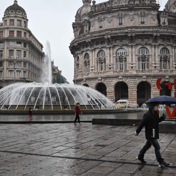 People wearing a protection mask walk across Piazza Raffaele de Ferrari in Genoa, Liguria, on March 13, 2020. (MARCO BERTORELLO/AFP via Getty Images)
