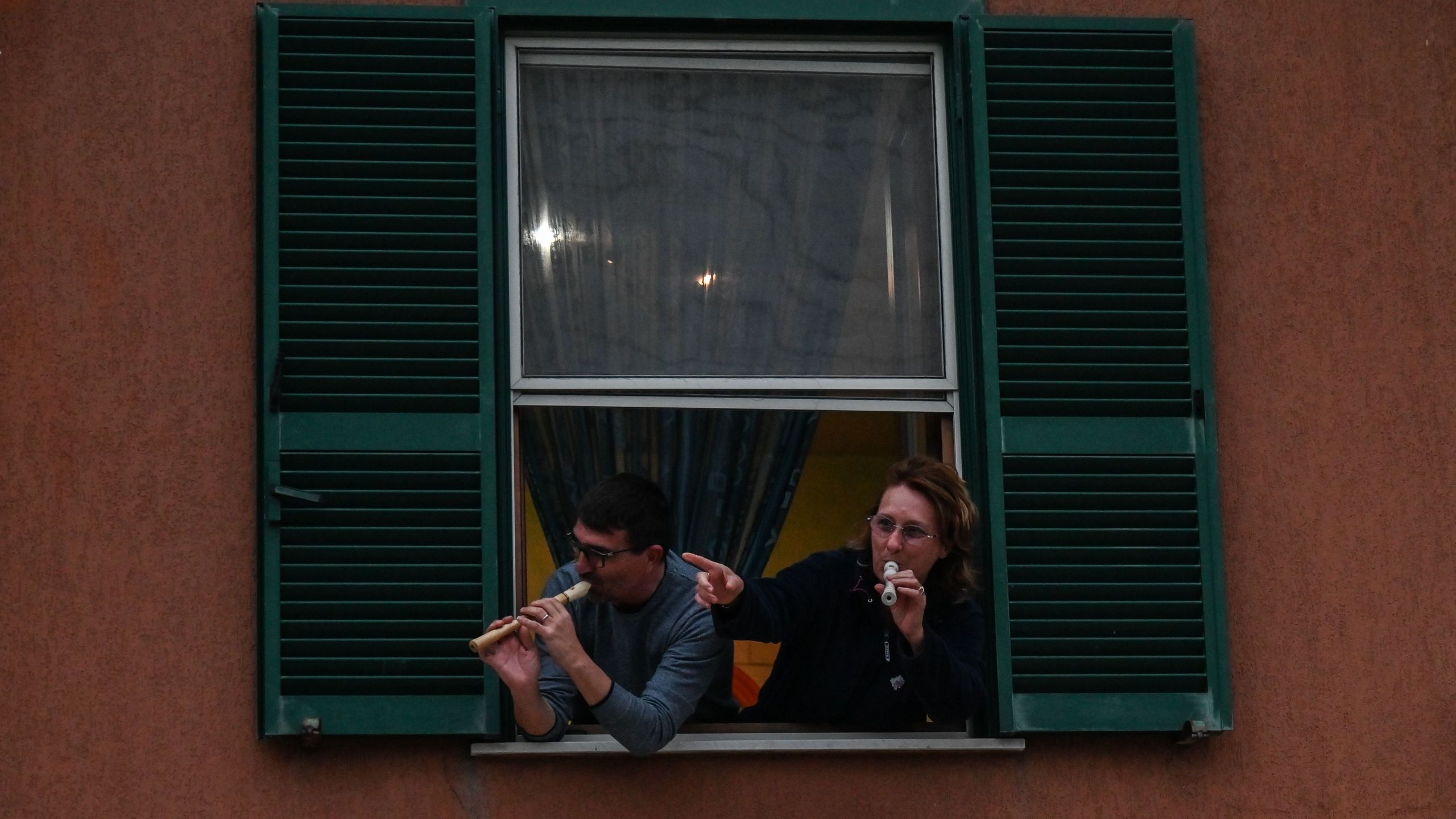 People play the Italian national anthem with from the window of their house in Rome during a music flash mob aimed at livening up the city's silence during the coronavirus lockdown, on March 13, 2020. (Credit: Andreas Solaro / AFP / Getty Images)
