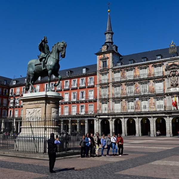 A group of people pose for a photo at the usually overcrowded Plaza Mayor in central Madrid on March 14, 2020 after regional authorities ordered all shops in the region be shuttered through March 26. (JAVIER SORIANO/AFP via Getty Images)