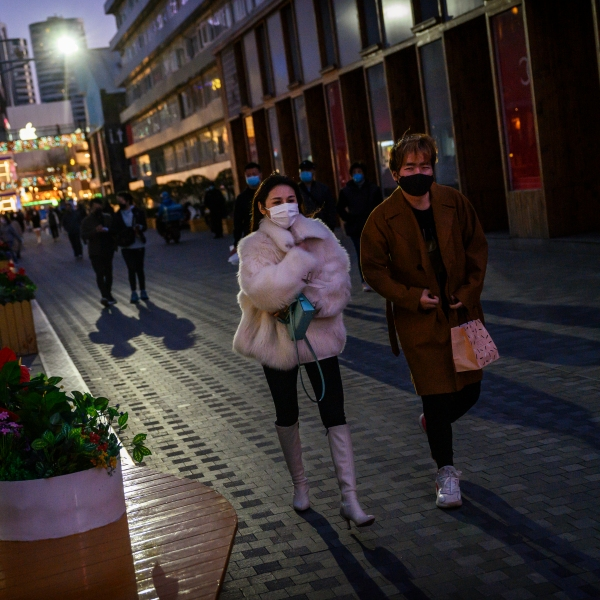 Chinese shoppers wear protective masks as they walk in a shopping area on March 14, 2020 in Beijing, China. (Kevin Frayer/Getty Images)