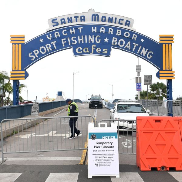 A police vehicle and security guard man the entrance to a closed Santa Monica Pier, one of the most popular tourist attractions in southern California on March 16, 2020 in Santa Monica, California. (FREDERIC J. BROWN/AFP via Getty Images)
