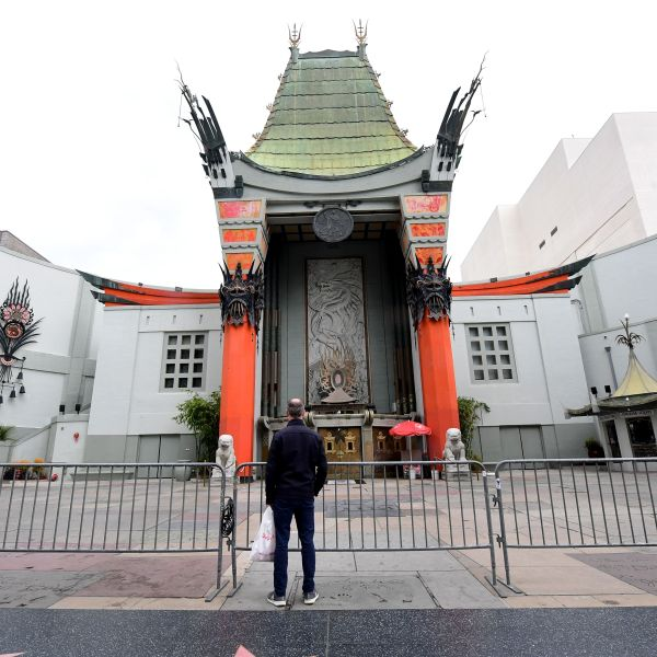 A man stands behind barricades in front of a temporarily closed TCL Chinese Theater in Hollywood on March 16, 2020, as the Coronavirus pandemic brings much of California to a standstill. (FREDERIC J. BROWN/AFP via Getty Images)