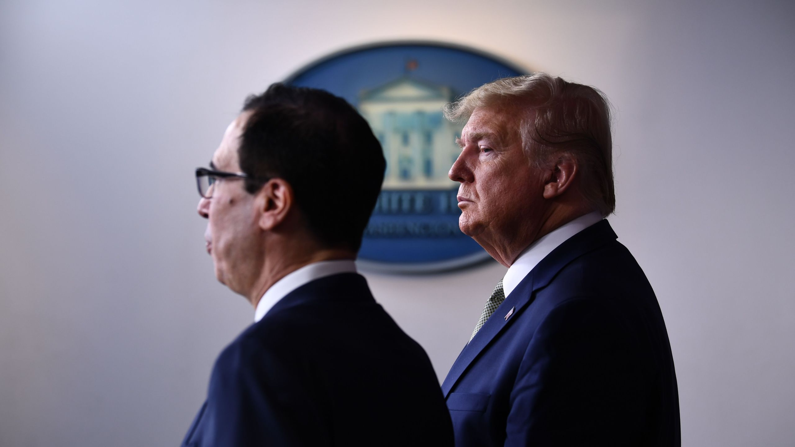 Donald Trump listens as Treasury Secretary Steven Mnuchin speaks during the daily press briefing on the Coronavirus pandemic situation at the White House on March 17, 2020 in Washington, D.C. (BRENDAN SMIALOWSKI/AFP via Getty Images)