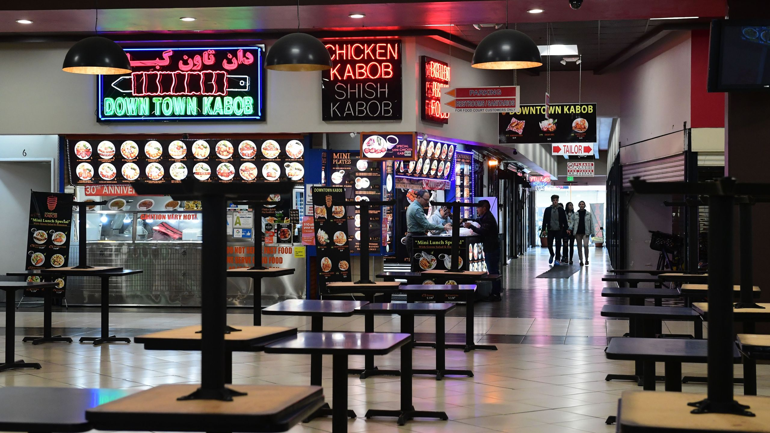Patrons arrive at a closed food court in Los Angeles where tables are placed on top of tables but takeout orders are available on March 17, 2020, as the coronavirus epidemic leads to restaurant and school closures. (Credit: Frederic J. Brown / AFP / Getty Images)