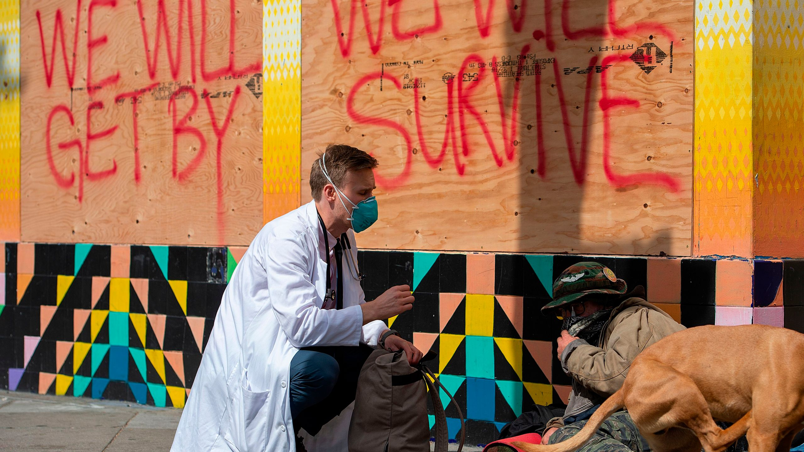 Stuart Malcolm, a doctor with the Haight Ashbury Free Clinic, speaks with homeless people in San Francisco about the coronavirus on March 17, 2020. (Credit: Josh Edelson / AFP / Getty Images)