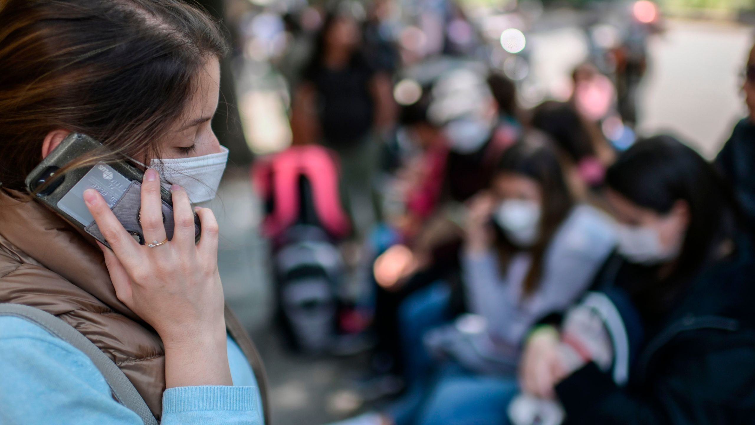 A woman wearing a face mask speaks on her mobile phone as she waits outside the consulate of Peru in Mexico City, on March 18, 2020. (Pedro Pardo/AFP via Getty Images)