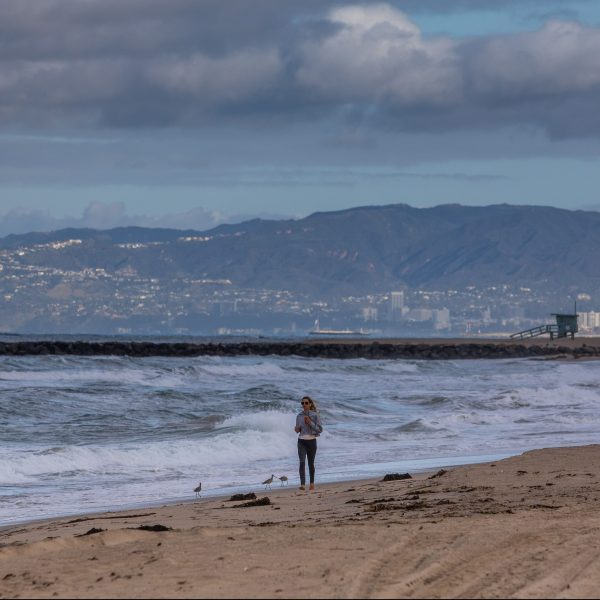 A woman runs in the morning on a deserted beach in El Segundo on March 19, 2020, as the region was gripped the coronavirus crisis. (Apu Gomes / AFP / Getty Images)
