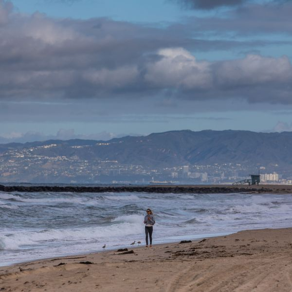 A woman runs in the morning on a deserted beach in El Segundo beach on March 19, 2020, as the region was gripped the coronavirus crisis. (APU GOMES/AFP via Getty Images)