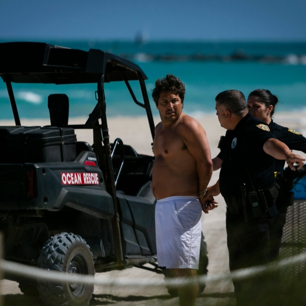 Police officers detain a man who allegedly trespassed into a closed beach at South Beach, Fla., on March 19, 2020. - In response to the virus's spread, Miami Beach and Fort Lauderdale are closing down parts of their public beaches and limiting the hours of operations for bars, clubs and restaurants to stifle the spread of coronavirus. (Eva Marie UZCATEGUI / AFP via Getty Images)