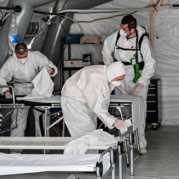 A view taken on March 20, 2020, in Cremona, southeast of Milan, shows cleaning personnel in protective gear disinfecting patients' beds in one of the tents from a newly operative field hospital for coronavirus patients, financed by U.S. evangelical Christian disaster relief group, Samaritans Purse. (MIGUEL MEDINA/AFP via Getty Images)