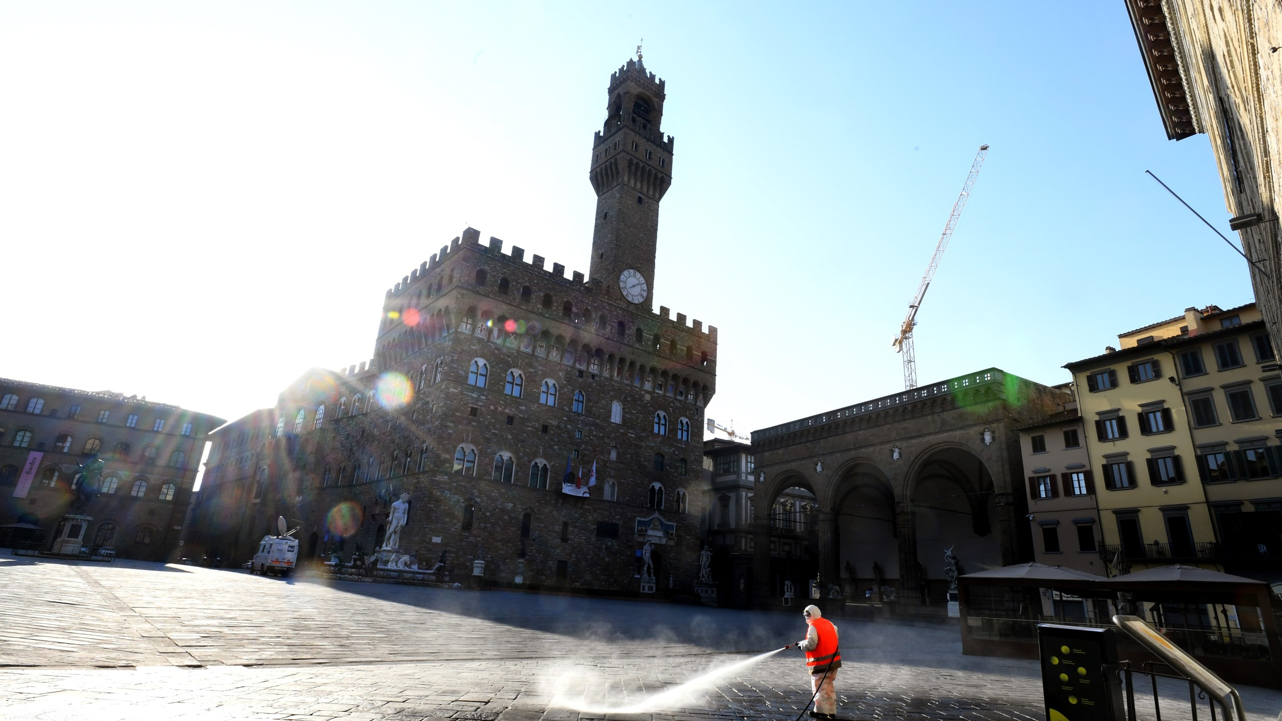 An employee of the municipal company disinfects the street in front of the Palazzo Vecchio in Florence on March 21, 2020. (Carlo Bressan/AFP via Getty Images)