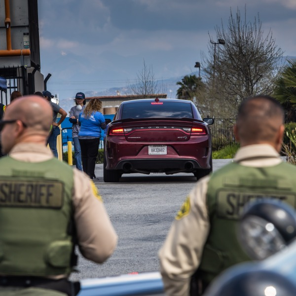 Police officers stand by as food service distribution workers talk to shoppers in a drive-thru at Jacmar Food Fest Sale in Industry, California on March 21, 2020. (APU GOMES/AFP via Getty Images)