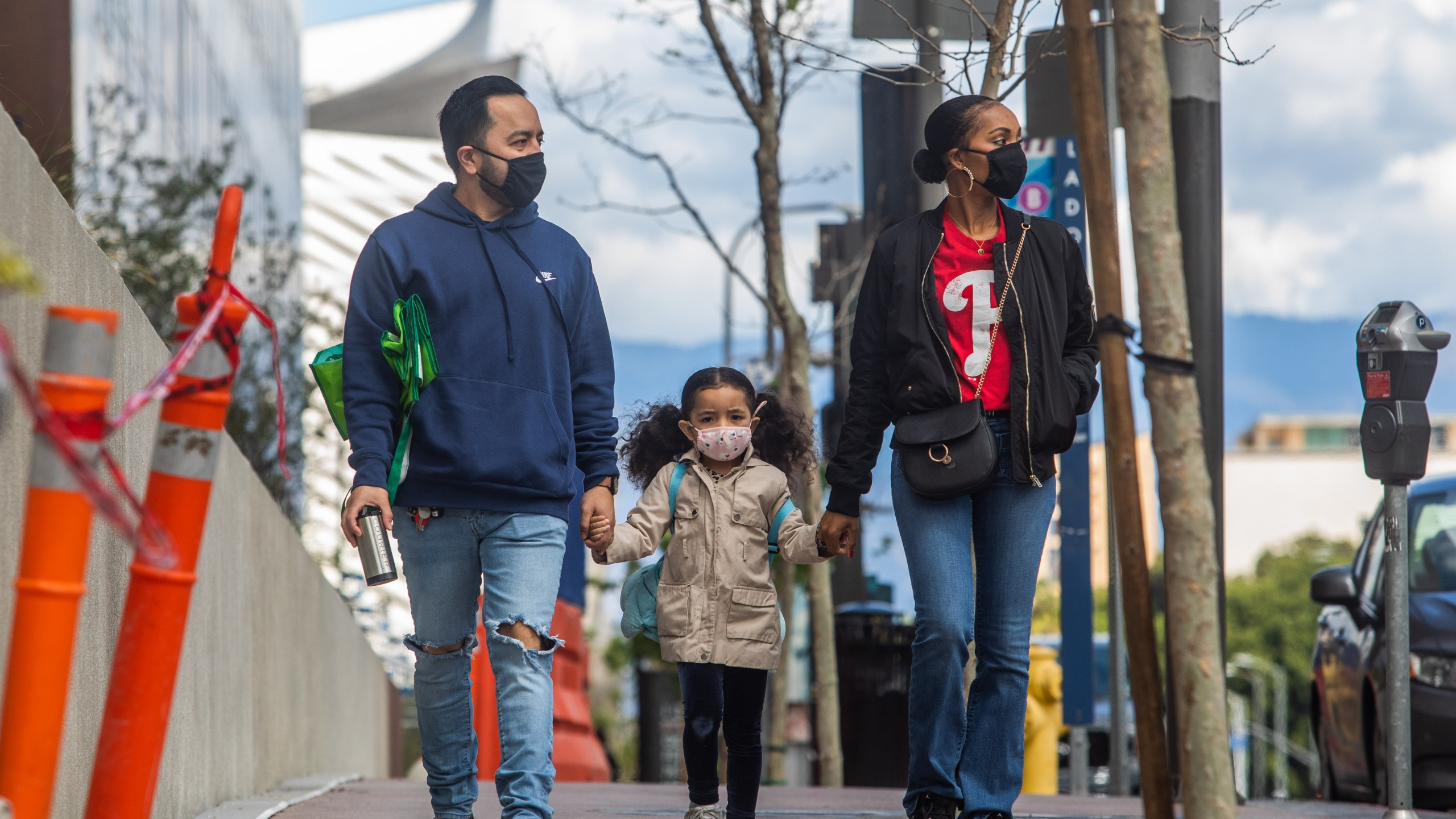 A family walks wearing masks in downtown Los Angeles on March 22, 2020, during the coronavirus outbreak. (APU GOMES/AFP via Getty Images)
