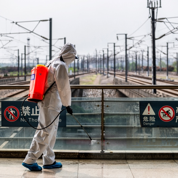 A crew member sprays disinfectant at Wuhan Railway Station in Wuhan in China's central Hubei province on March 24, 2020. (STR/AFP via Getty Images)