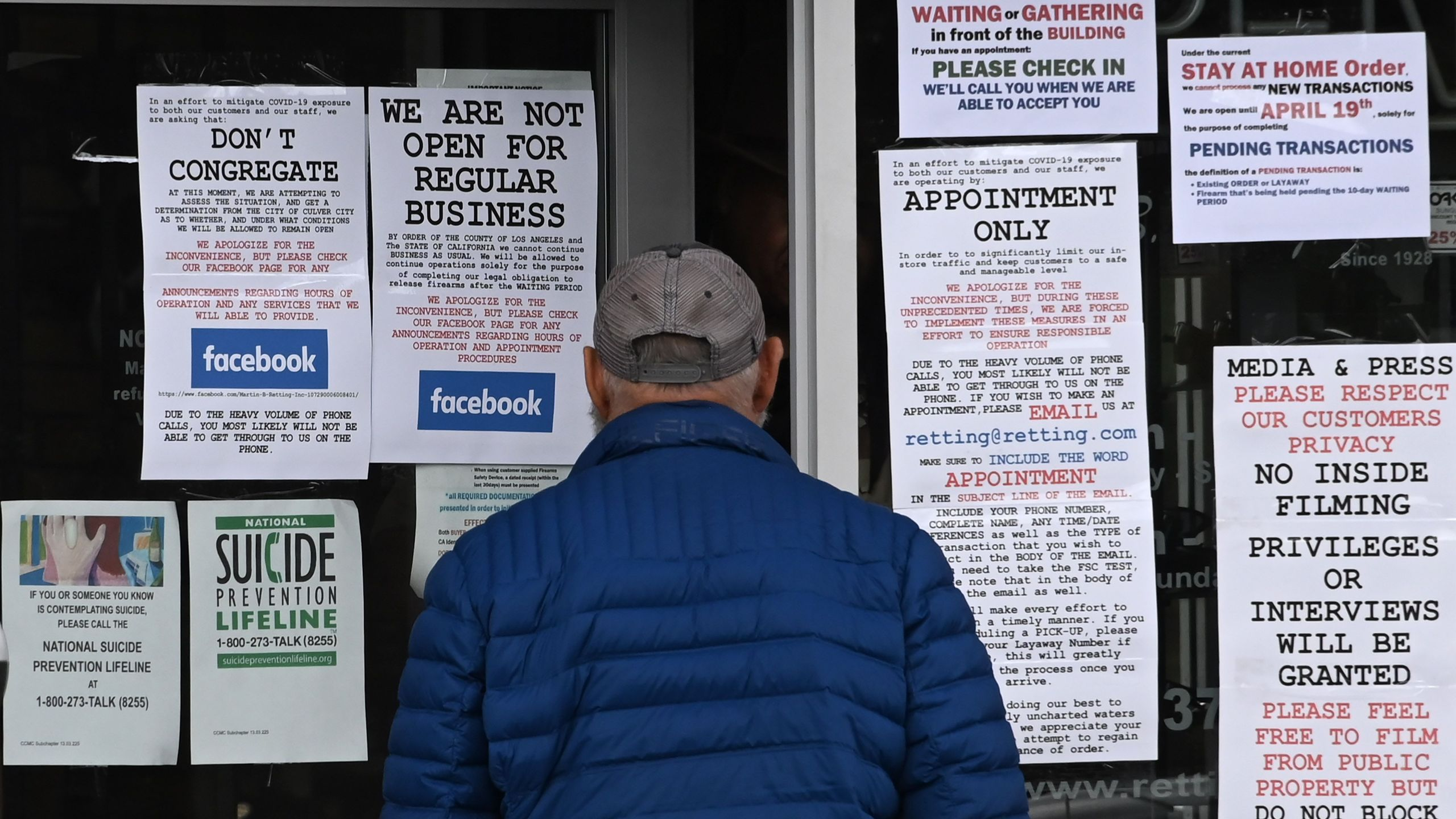 A man reads signs on the entrance to Martin B. Retting gun shop in Culver City on March 24, 2020. (Robyn Beck / AFP / Getty Images)