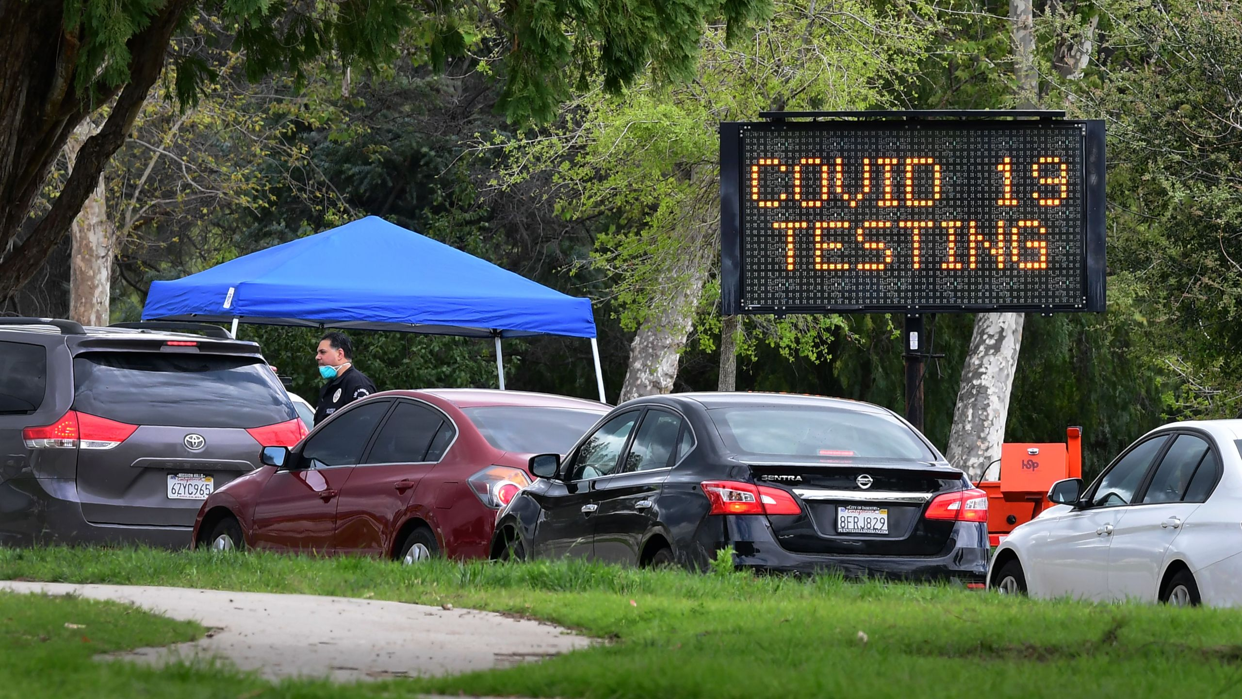 A police officer mans the entrance to a coronavirus testing center in Hansen Dam Park on March 25, 2020, in Pacoima, California. (FREDERIC J. BROWN/AFP via Getty Images)