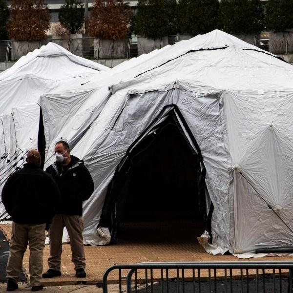 People speak near a makeshift morgue outside of Bellevue Hospital on March 25, 2020 in New York City, New York. (Eduardo Munoz Alvarez/Getty Images)