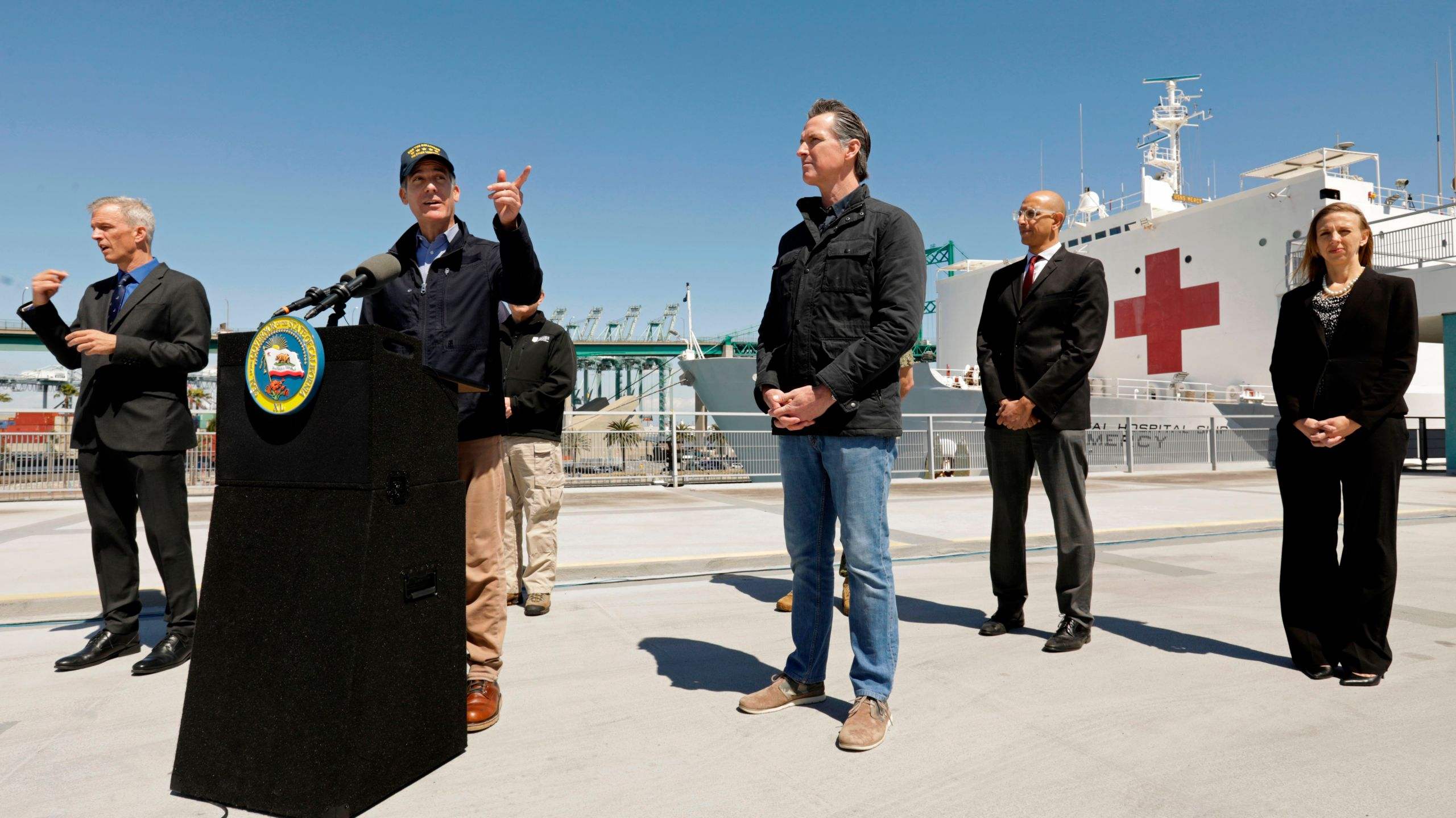 Gov. Gavin Newsom listens as Los Angeles Mayor Eric Garcetti speaks in front of the USNS Mercy hospital ship after it arrived into the Port of Los Angeles on March 27, 2020. (CAROLYN COLE/POOL/AFP via Getty Images)
