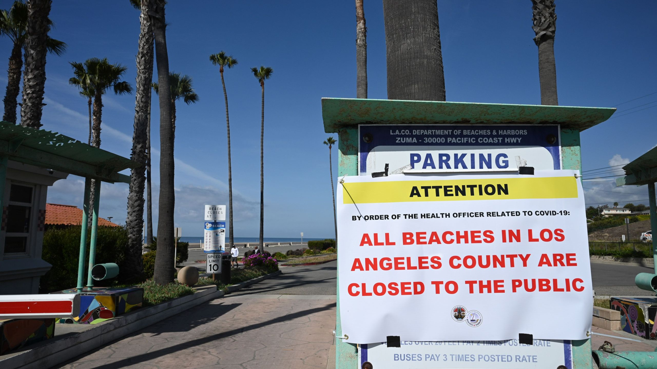 A sign reads that Zuma Beach in Malibu is closed to the public on March 28, 2020, in an effort to stem the growth of COVID-19 cases in Los Angeles County. (ROBYN BECK/AFP via Getty Images)