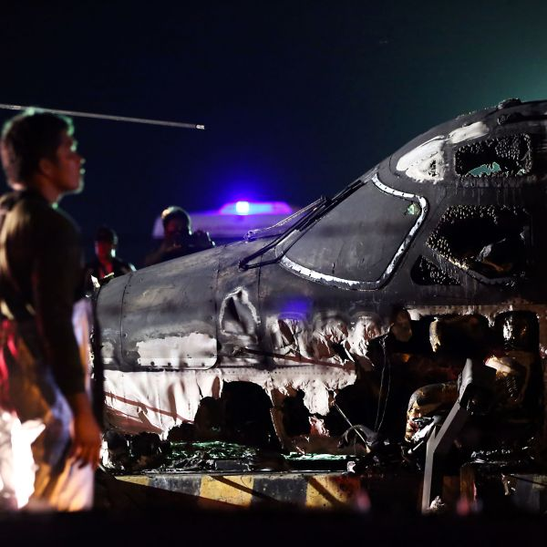 Rescuers stand next to the wreckage of a Westwind aircraft after it caught fire during takeoff at Manila International Airport in Manila on March 29, 2020. (AFP via Getty Images)