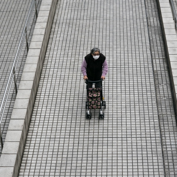 An elderly woman pushes a cart through the Tokyo Metropolitan Government building in Japan on Feb. 26, 2020. (Credit: Tomohiro Ohsumi / Getty Images)
