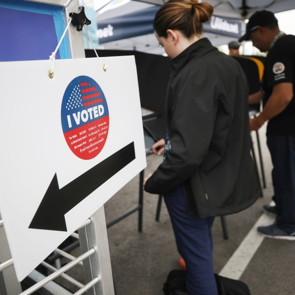 Voters prepare their ballots during early voting for the California presidential primary election outside Universal Studios Hollywood on Feb. 27, 2020. (Credit: Mario Tama / Getty Images)