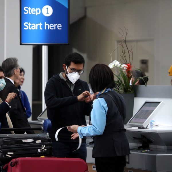 Passengers wear protective masks as they check into an international flight at San Francisco International Airport on March 6, 2020, in San Francisco. (Justin Sullivan/Getty Images)