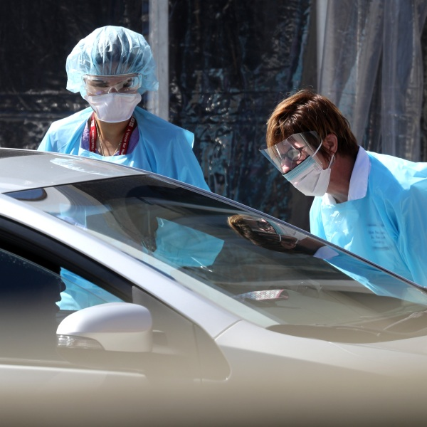 Medical personnel take a sample from a person at a drive-thru Coronavirus COVID-19 testing station at a Kaiser Permanente facility on March 12, 2020 in San Francisco. (Justin Sullivan/Getty Images)