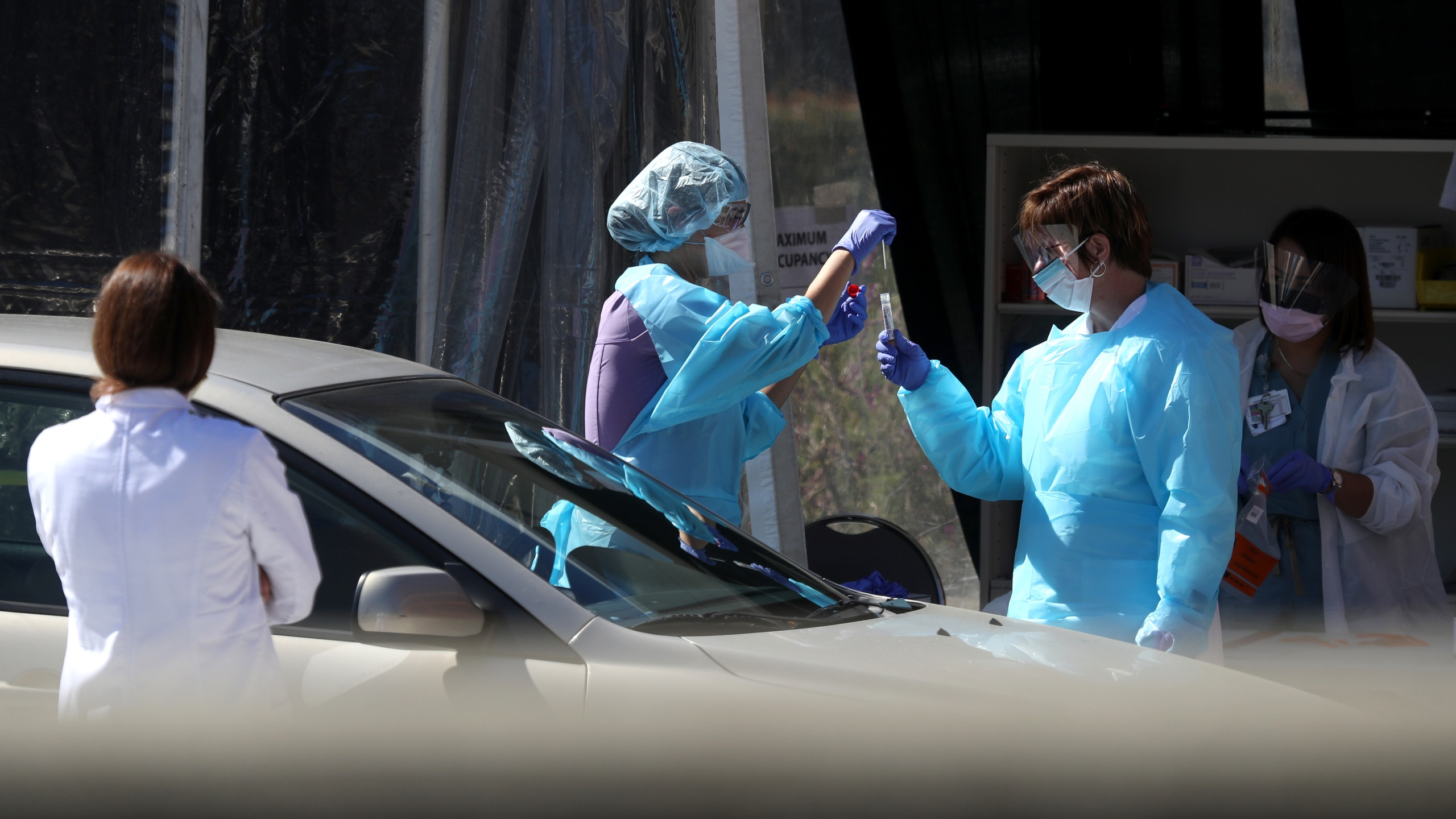Medical personnel take a sample from a person at a drive-thru coronavirus testing station at a Kaiser Permanente facility on March 12, 2020 in San Francisco. (Justin Sullivan/Getty Images)