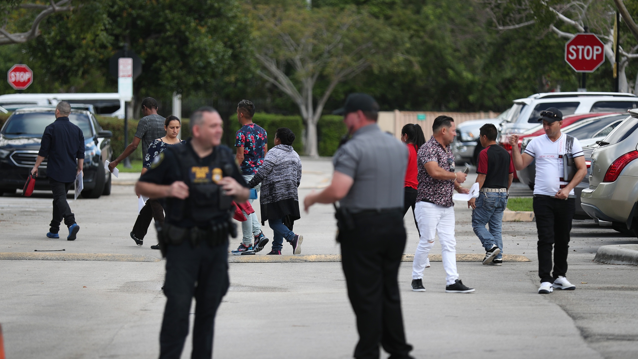 People walk through the parking lot outside the U.S. Immigration and Customs Enforcement office in Miramar, Florida, on March 13, 2020. (Credit: Joe Raedle / Getty Images)