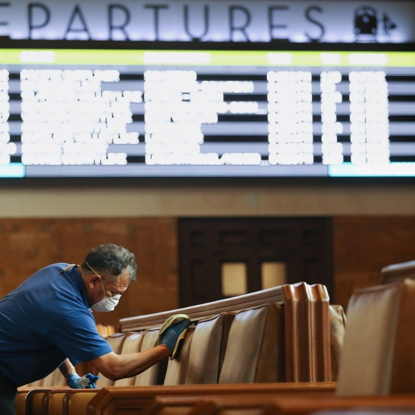 An employee cleans seats in a waiting area at Union Station on March 13, 2020, in Los Angeles.(Mario Tama/Getty Images)